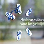 Afbeelding waar de sticker van het Nederlands Keurmerk voor Toegankelijkheid te zien is op een winkelruit.