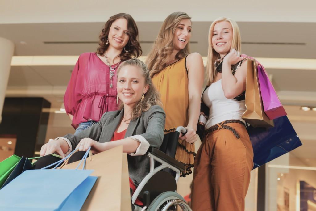 Foto van jonge meiden die aan het winkelen zijn waarvan er één in een rolstoel zit.