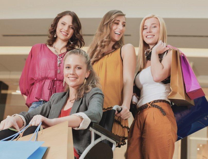 Groep vriendinnen met een in een rolstoel winkelen samen